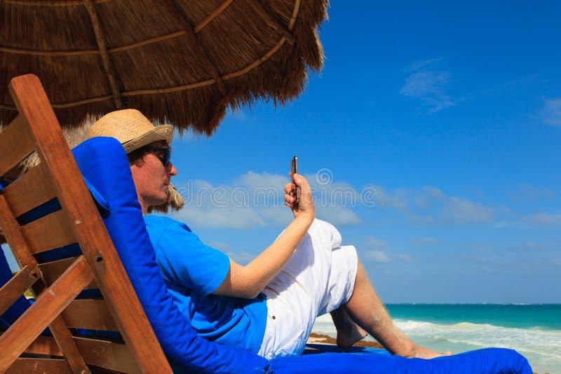 Hombre con el teléfono celular en la playa tropical fotos de archivo libres de regalías