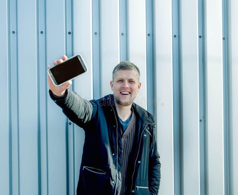 Hombre con el teléfono móvil en fondo urbano imágenes de archivo libres de regalías
