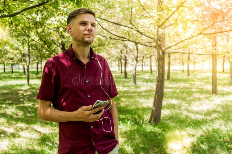 Hombre con el teléfono móvil en parque del verano Hombre hermoso joven con el SM fotografía de archivo libre de regalías