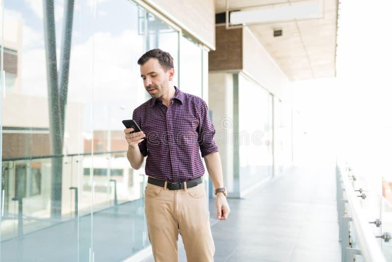 Hombre con el teléfono móvil que comprueba el uso de Internet en compras imagen de archivo