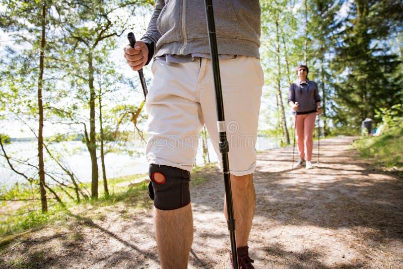 Hombre con el vendaje en la rodilla, el caminar nórdico foto de archivo libre de regalías