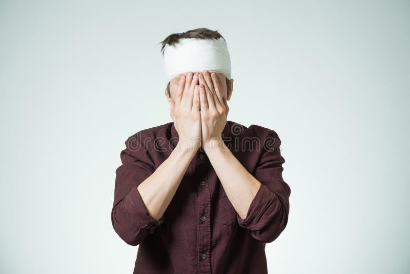 Hombre con el vendaje en su cabeza imagenes de archivo