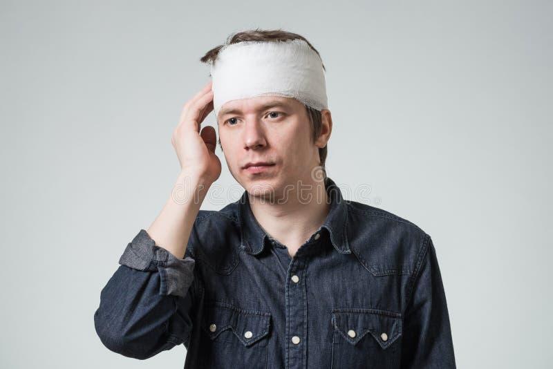 Hombre con el vendaje en su cabeza imagen de archivo