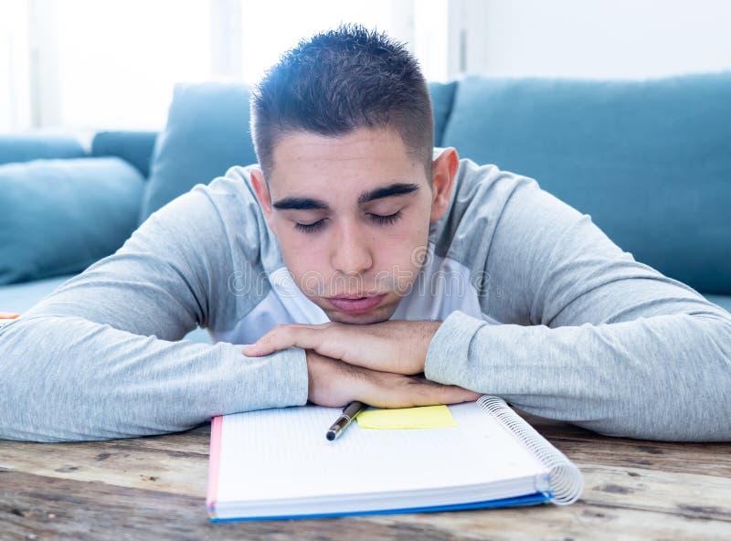 Hombre con exceso de trabajo y cansado del estudiante de la escuela secundaria que estudia la sensaci?n casera deprimida y desesp fotos de archivo