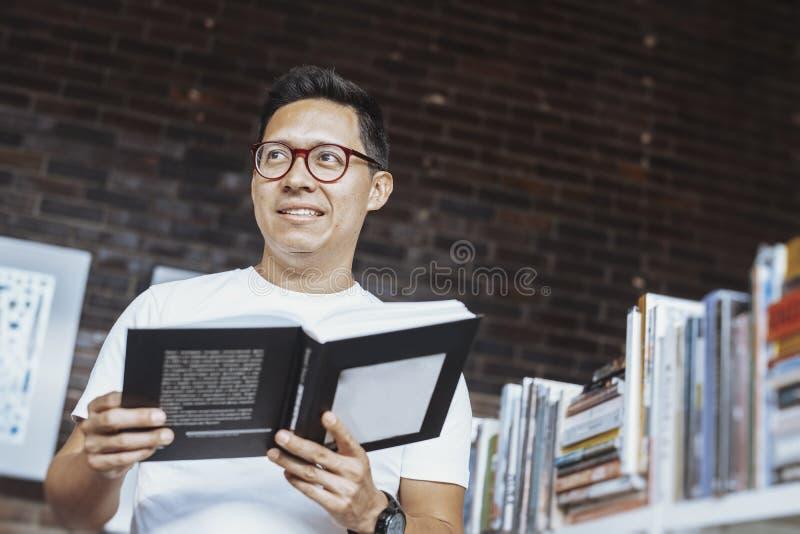 Hombre con gafas pensativo joven que sostiene el libro y que mira a un lado fotos de archivo