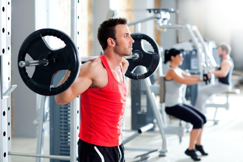 Hombre con gimnasia del equipo de entrenamiento del peso de la pesa de gimnasia fotos de archivo libres de regalías