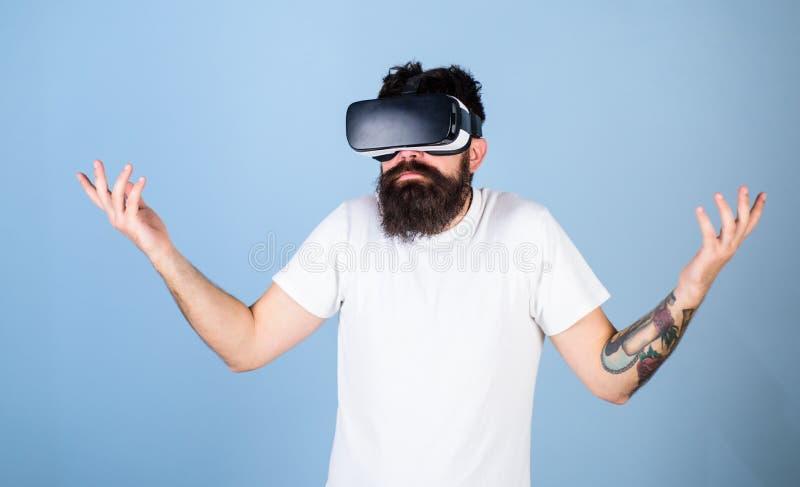 Hombre con la barba del inconformista en postura del idk aislada en fondo azul Desarrollador de software barbudo desorientado sob fotografía de archivo