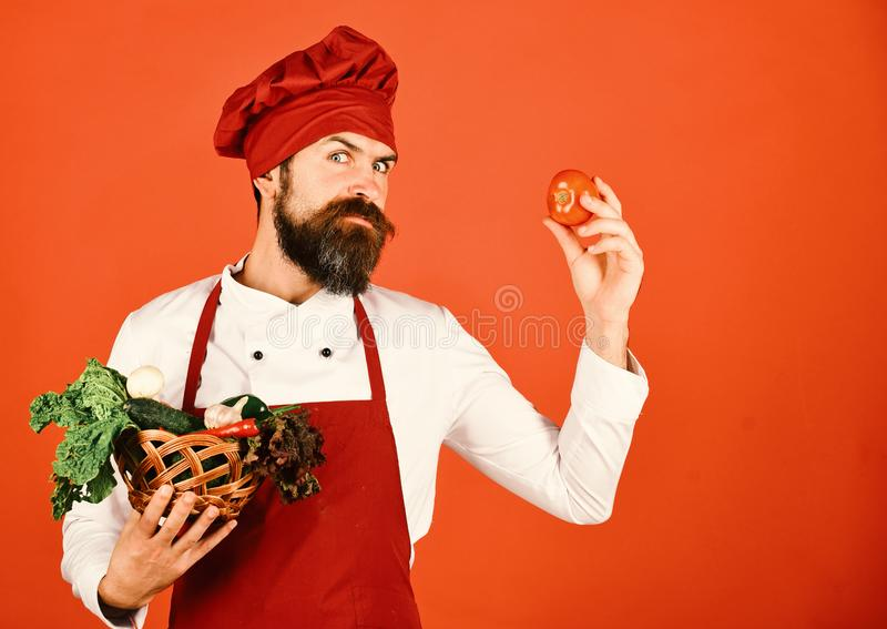 Hombre con la barba en fondo rojo El cocinero sostiene la lechuga, ajo imagen de archivo