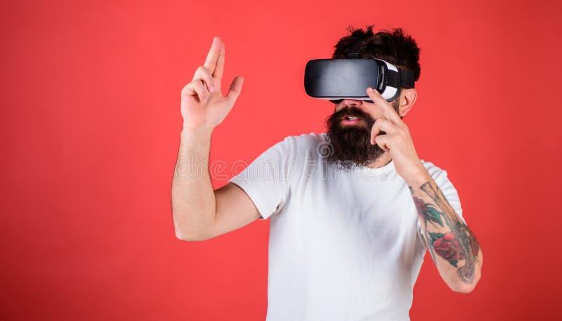 Hombre con la barba en los vidrios de VR que tiran, fondo rojo Concepto virtual de la galería de tiroteo Individuo con la exhibic foto de archivo libre de regalías