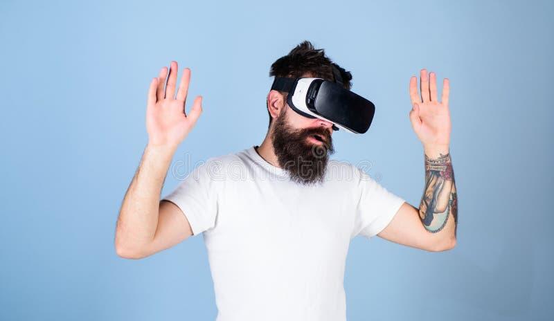 Hombre con la barba en vidrios de VR, fondo azul claro Inconformista en cara ocupada que explora realidad virtual con el artilugi fotos de archivo
