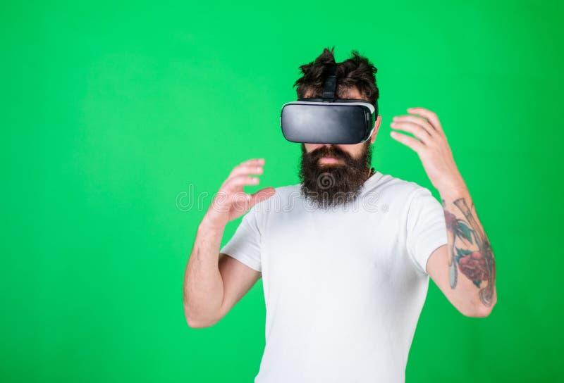 Hombre con la barba en vidrios de VR, fondo verde Inconformista en cara ocupada que explora realidad virtual con el artilugio int imagen de archivo libre de regalías