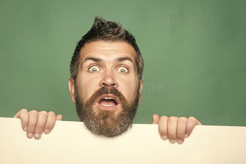 Hombre con la barba larga en cara sorprendida con el papel foto de archivo