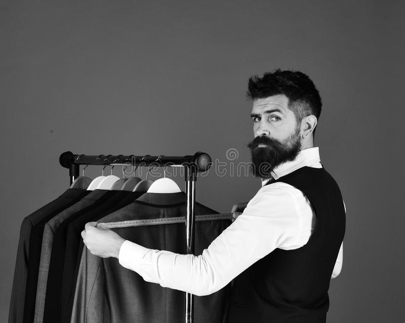 Hombre con la barba por el estante de la ropa El diseñador toma medidas foto de archivo libre de regalías