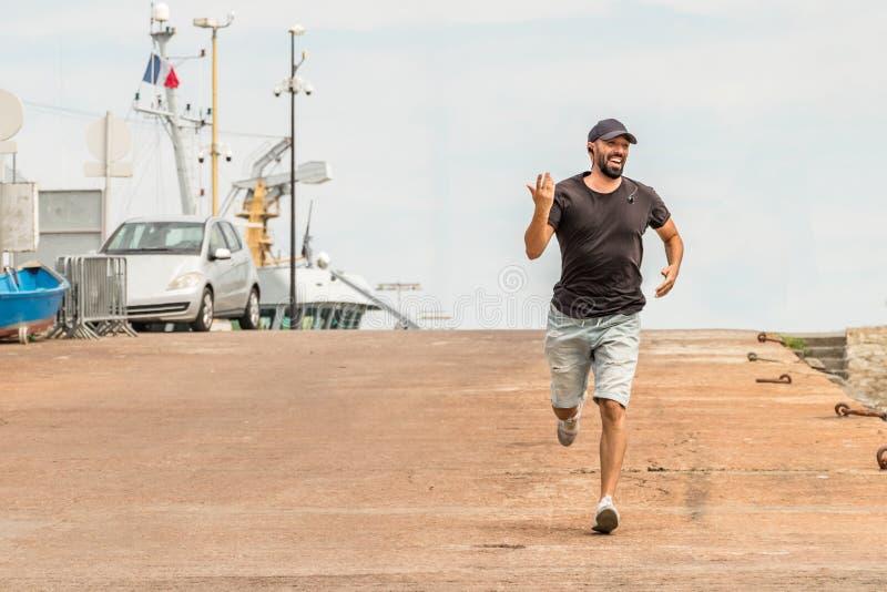 hombre con la barba que corre en la calle que habla con los auriculares inalámbricos - auriculares imágenes de archivo libres de regalías