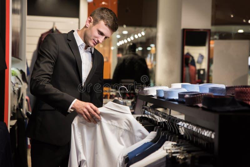 Hombre con la barba que elige la camisa en una tienda imagen de archivo