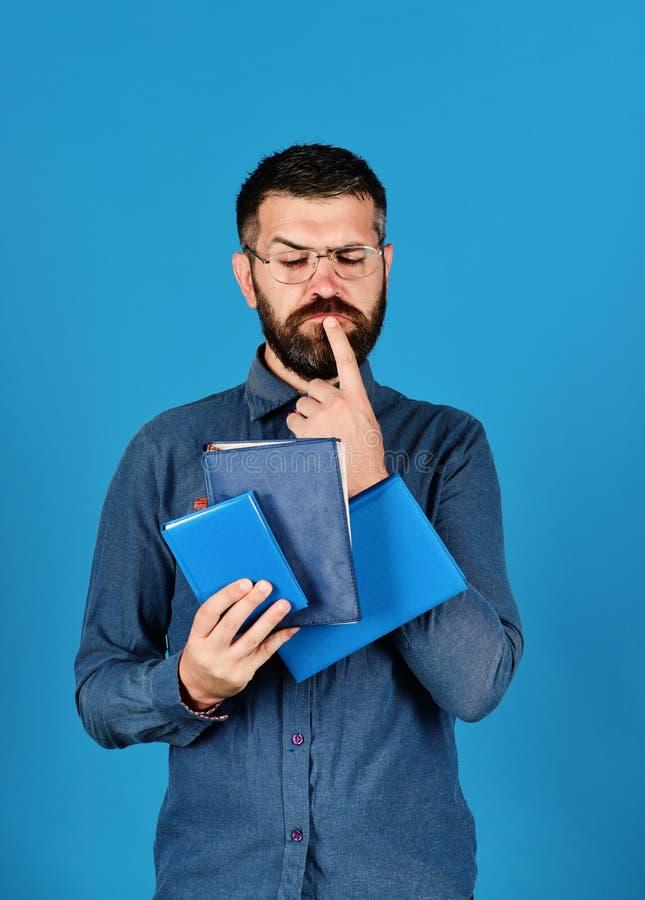 Hombre con la barba y los libros Cuadernos en color azul fotos de archivo