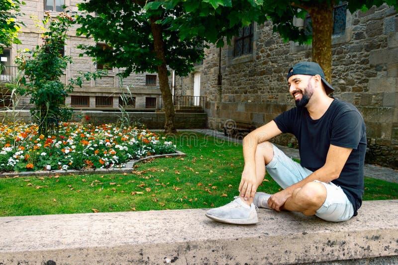 Hombre con la barba y snapback, sentándose en la calle que mira lejos, feliz, relajado, disfrute, concepto del ocio foto de archivo