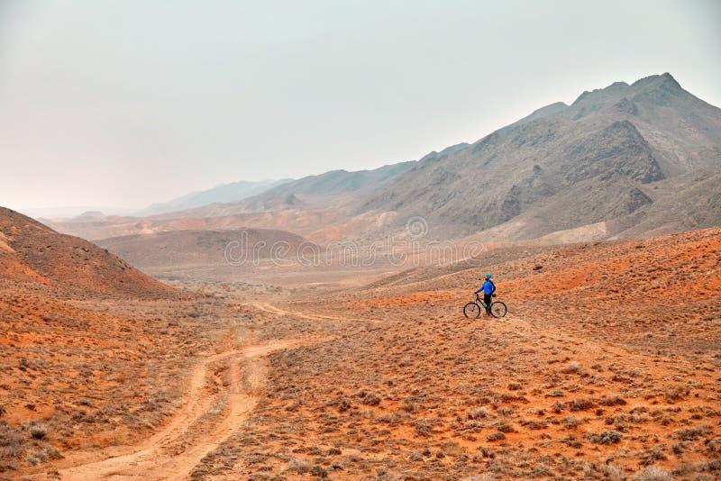 Hombre con la bici de montaña en el desierto fotografía de archivo libre de regalías