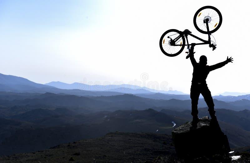 Hombre con la bici que se coloca en canto de la montaña imagen de archivo