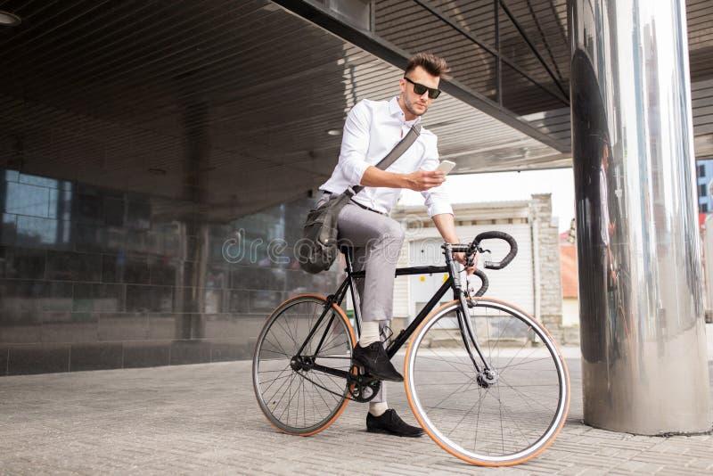 Hombre con la bicicleta y smartphone en la calle de la ciudad fotos de archivo