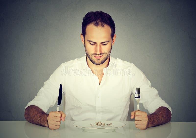 Hombre con la bifurcación y cuchillo que se sienta en la tabla que mira la placa vacía foto de archivo libre de regalías