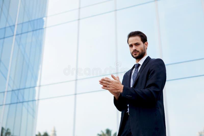 Hombre con la buena sensación que coloca el edificio de oficinas cercano imagen de archivo libre de regalías