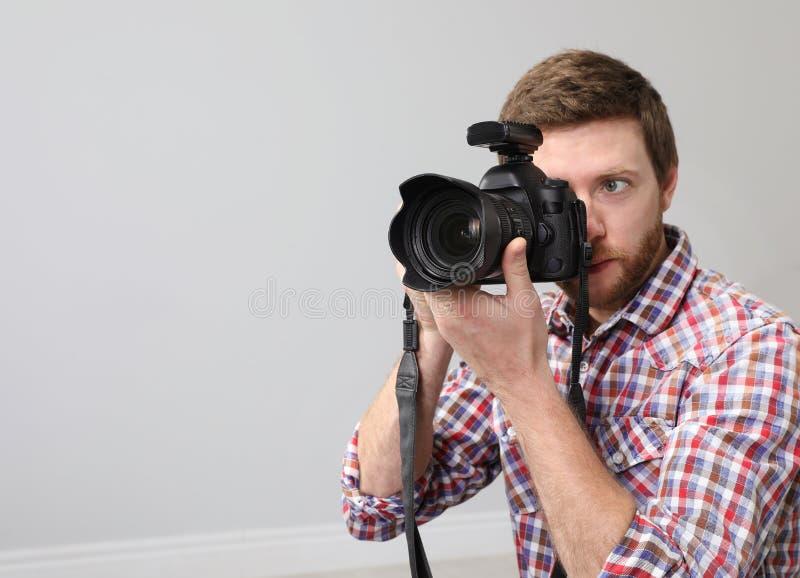 Hombre con la cámara profesional en estudio de la foto imagenes de archivo