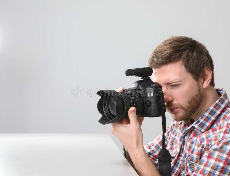 Hombre con la cámara profesional en estudio de la foto foto de archivo