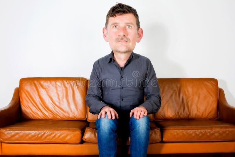 Hombre con la cabeza grande que se sienta en el sofá y esperar fotografía de archivo libre de regalías
