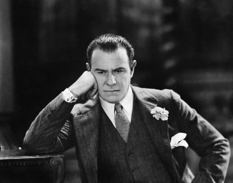 Hombre con la cabeza que se inclina contra su pensamiento de la mano (todas las personas representadas no son vivas más largo y n imagen de archivo