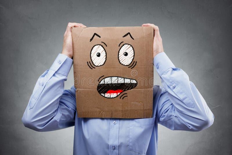 Hombre con la caja de cartón en su cabeza que muestra la expresión chocada y sorprendida imagenes de archivo