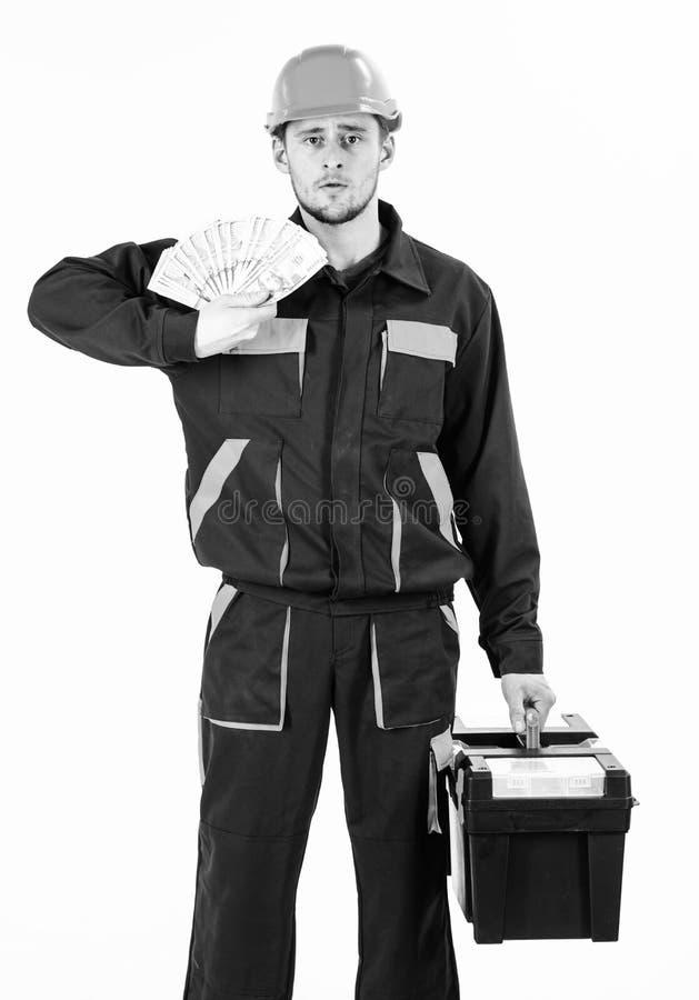 Hombre con la caja de herramientas aislada en el fondo blanco El constructor gana el dinero, reparador sostiene billetes de banco fotografía de archivo