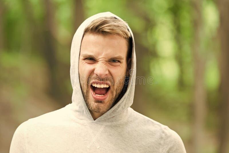 Hombre con la cerda en la cara de grito, fondo de la naturaleza, defocused Concepto del cuidado de piel Hombre con la barba o mir foto de archivo