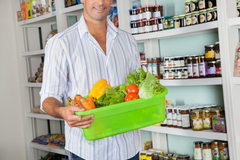 Hombre con la cesta de verduras frescas que se colocan adentro imagen de archivo libre de regalías
