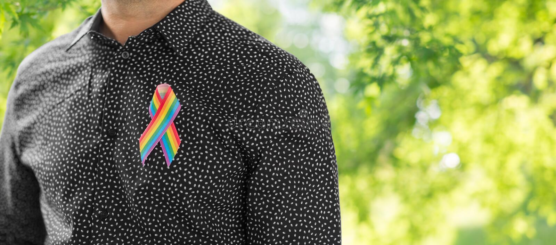 Hombre con la cinta de la conciencia del arco iris del orgullo gay imágenes de archivo libres de regalías