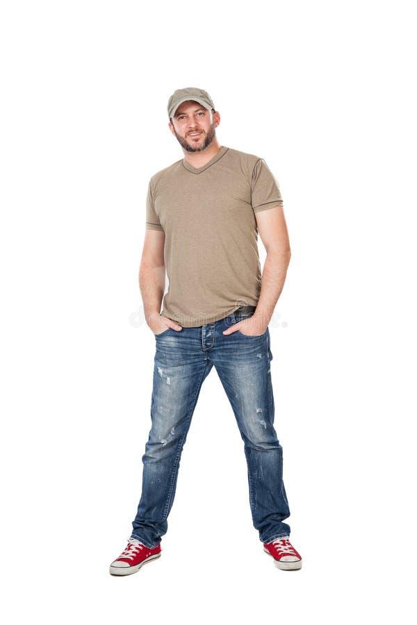 Hombre con la colocación del sombrero, de la camiseta y de los vaqueros, aislada en blanco foto de archivo libre de regalías