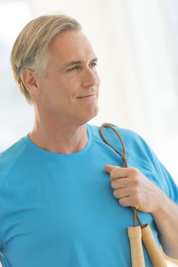 Hombre con la comba que mira lejos en club de salud foto de archivo