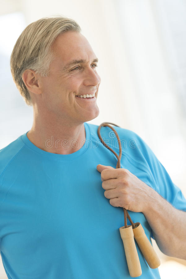 Hombre con la comba que mira lejos en gimnasio imagen de archivo