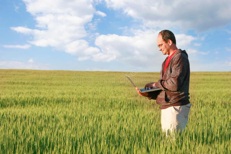 Hombre con la computadora portátil en campo fotografía de archivo libre de regalías