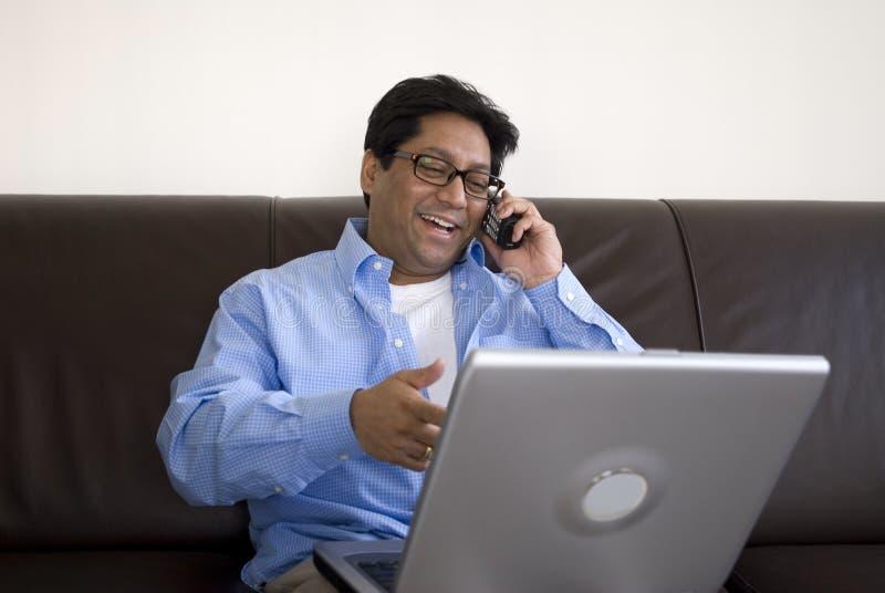 Hombre con la computadora portátil en el teléfono fotografía de archivo libre de regalías