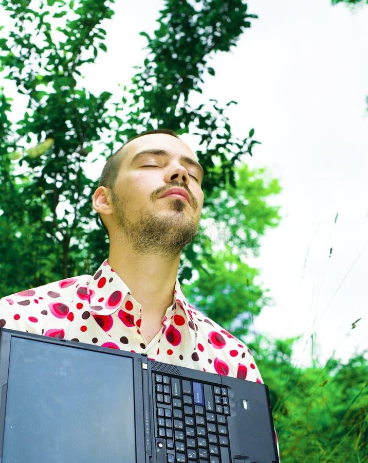 Hombre con la computadora portátil en jardín imagen de archivo