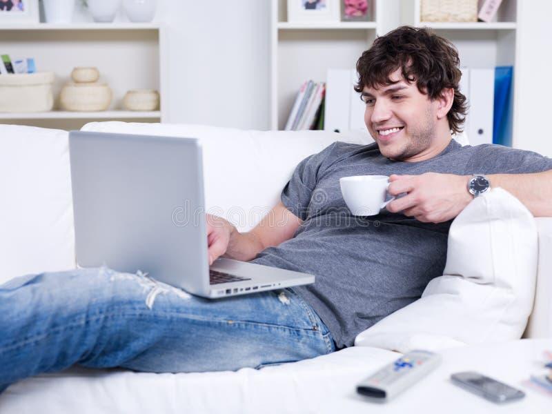Hombre con la computadora portátil y la taza de café imagenes de archivo
