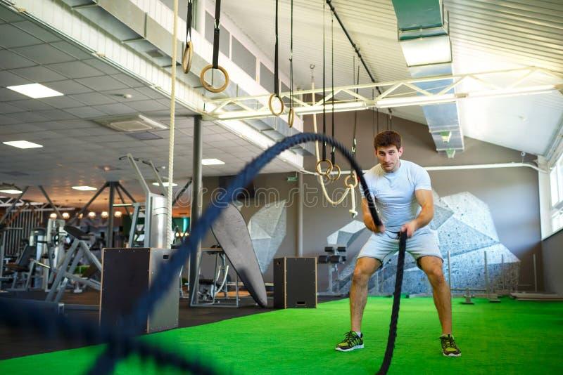 Hombre con la cuerda de la batalla en gimnasio funcional de la aptitud del entrenamiento foto de archivo