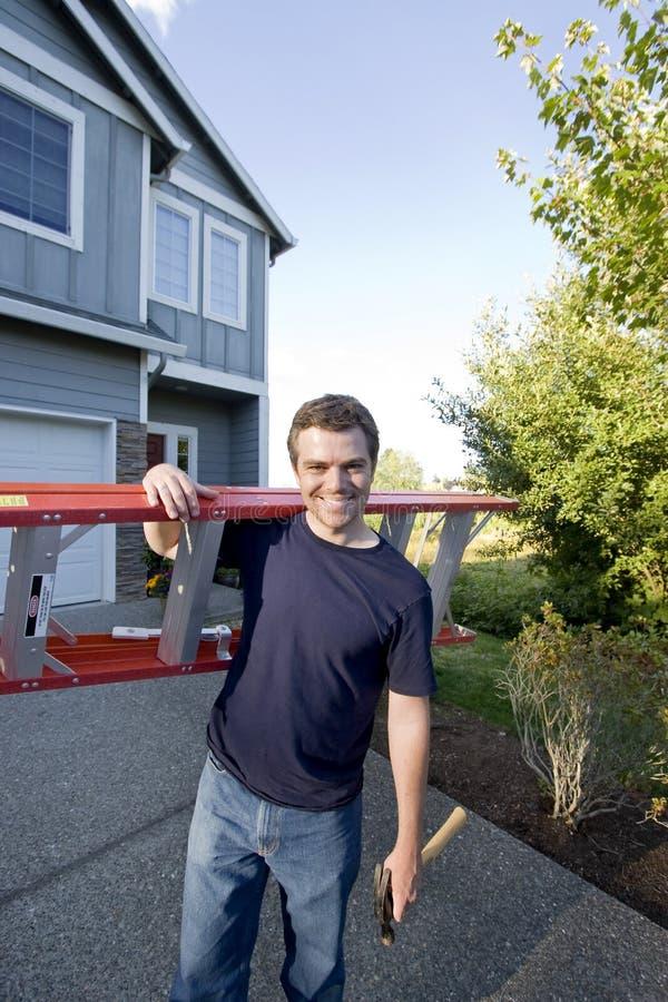 Hombre con la escala y el martillo - vertical imagen de archivo libre de regalías