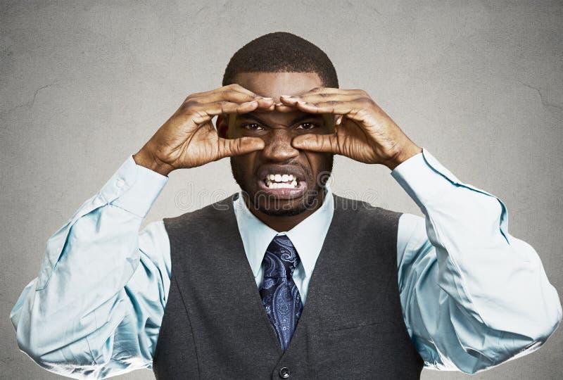 Hombre con la expresión asqueada de la cara, mirando a través de binocul de la mano imagen de archivo libre de regalías