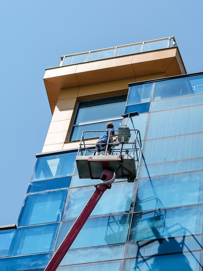 Hombre con la fregona que lava una pared de cristal azul de la plataforma del autotower o de trabajo aéreo en un día de verano so foto de archivo