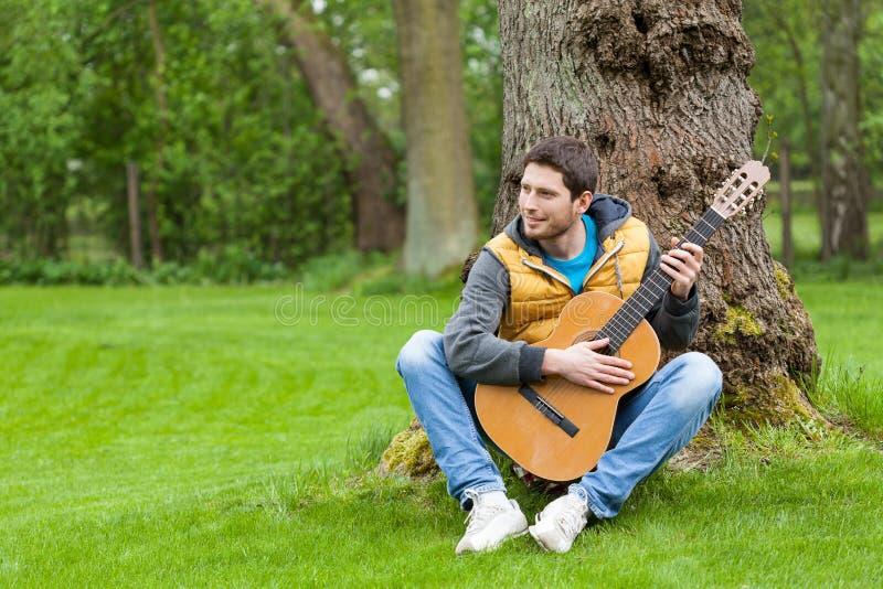 Hombre con la guitarra en jardín foto de archivo libre de regalías