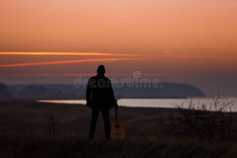 Hombre con la guitarra en puesta del sol fotografía de archivo libre de regalías