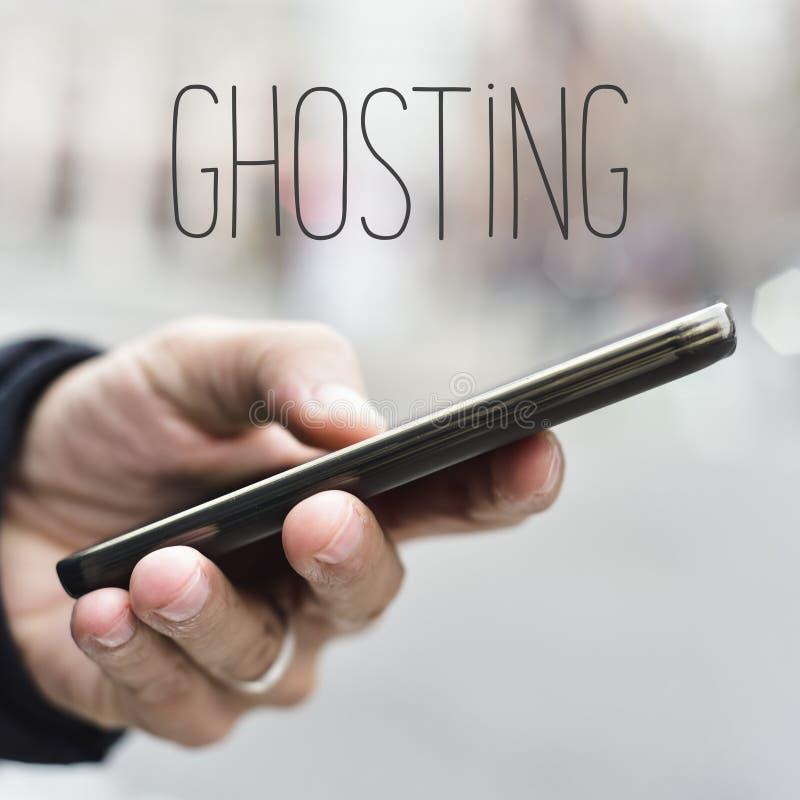 Hombre con la imagen secundaria del smartphone y del texto imagen de archivo