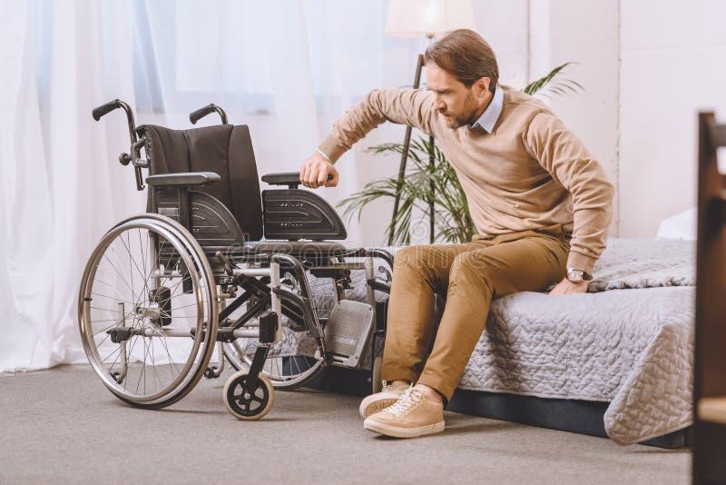 hombre con la incapacidad que intenta sentarse en la silla de ruedas imagenes de archivo
